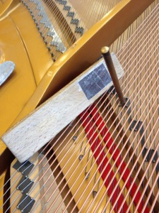 Tapping strings to bridge using wood block